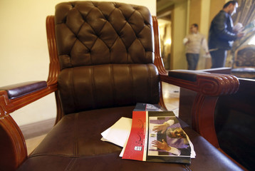 Members of Muslim Brotherhood walk nearby while torn book with picture of Egyptian President Mursi on its cover is seen on chair at Muslim Brotherhood headquarters in Cairo