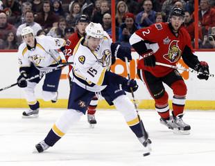 Nashville Predators' Smith takes a shot on net as teammate Smithson and Ottawa Senators' Condra and Cowen look on in Ottawa