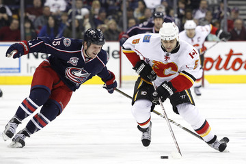 Calgary Flames' Mark Giordano fights for the puck with Columbus Blue Jackets' Derek Dorsett during the second period of their NHL hockey game in Columbus