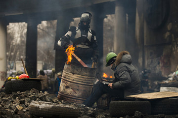 An anti-government protester uses a laptop at barricades facing riot police in Kiev