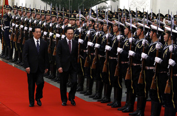 South Korean President Lee walks with his Chinese counterpart Hu as they inspect a guard of honour during an official welcoming ceremony in the Great Hall of the People in Beijing