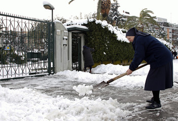 A nun shovels snow in front of her convent in Rome