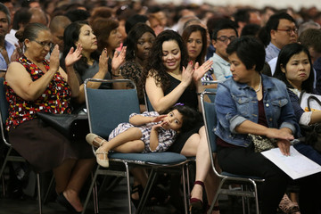 Immigrant Jeimy Reyes, 27, sits with her daughter Tiana Cervantes, 3, as she is sworn in as a new U.S. citizen at a naturalization ceremony in Los Angeles