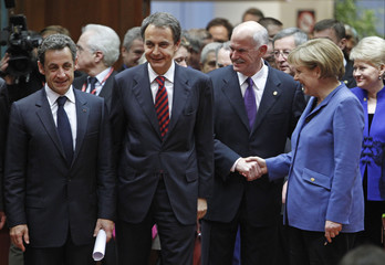 German Chancellor Merkel shakes hands with Greek Prime Minister Papandreou as French President Sarkozy and Spanish Prime Minister Zapatero look on at the start of a European Union leaders summit in Brussels