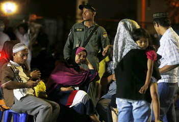 Family members sit outside Adam Malik hospital as they wait for the bodies of victims of an Indonesian military C-130 Hercules transport plane that crashed into a residential area in Medan