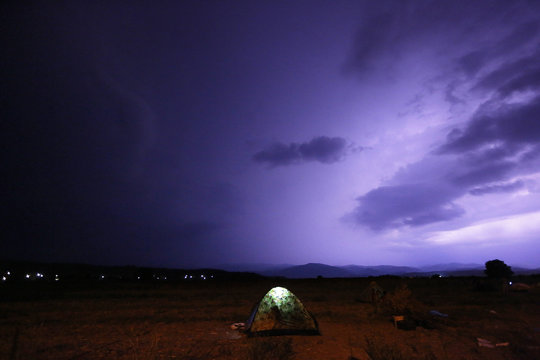 Refugees camp on a field as lightning illuminates the sky during a storm at the Greek-Macedonian border, near the village of Idomeni