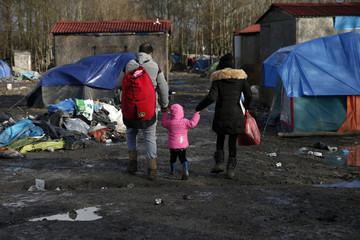 Migrants walks past shelters in a muddy field called the Grande-Synthe jungle near Dunkerque