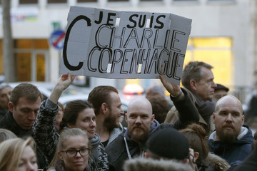 """People hold a placard which reads """"I am Charlie Copenhagen"""" as they gather to pay tribute outside the Danish embassy in Paris"""