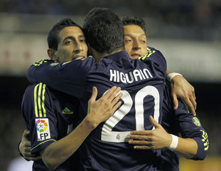 Real Madrid's Higuain celebrates with team mates Di Maria and Ozil after he scored against Valencia during their Spanish first division soccer match in Valencia