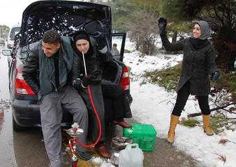 A girl throws a snow ball to a couple smoking a water pipe in al-Zabadani mountains north of Damascus