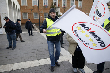 An activist waves a flag bearing the logo of the Five-Star Movement during a rally in Pomezia