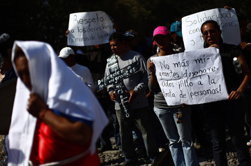Illegal immigrants carry signs as they take part in the re-enactment of the Passion of Christ in Huehuetoca
