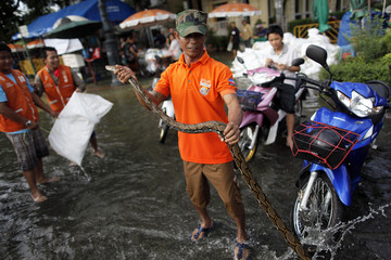 A man poses with a python he caught in floodwaters just outside the Grand Palace in Bangkok