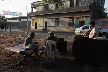 People gather on the streets outside their homes after an earthquake shook Managua