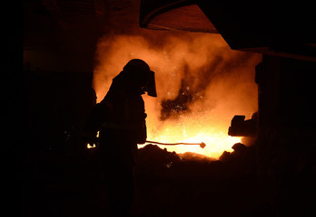 A man cleans the runners on the blast furnace at the SSI steel plant at Redcar