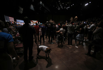 A supporter of Democratic U.S. presidential candidate Senator Bernie Sanders stands with his dog at the back of the rally as Sanders speaks to supporters on the night of the Michigan, Mississippi and other primaries at a Sanders campaign event in Miami