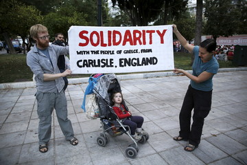 British visitors Hazel Graham, 34, and Shephen Graham, 35, display a banner they made next to their two and a half year old daughter Emily, during an anti-bailout protest in Athens, Greece