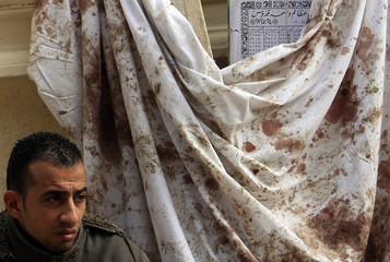 An Egyptian Christian stands beside a white cloth smeared with blood from victims during Saturday's bomb attacks in the Coptic Orthodox church in Alexandria