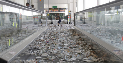 A boy skates through litter on the floor, caused by cleaning staff during protest, in Barcelona's airport