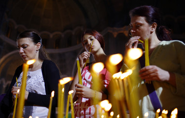 Women light candles during an Orthodox Easter service at the St. Sava's temple in Belgrade