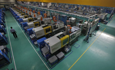 An employee walks past machines used to make auto parts at the factory of the Samvardhana Motherson Group in Noida