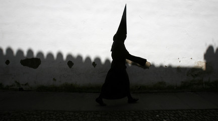 """A penitent heads to take part in a procession of the """"Los Dolores"""" brotherhood during Holy Week in Cordoba"""