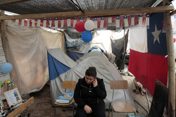 A relative talks on a mobile phone in her tent at the relatives camp where they are living at San Jose copper and gold mine