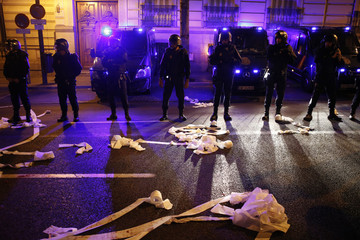 Toilet paper lies strewn on the ground in front of Spanish riot police standing guard outside the headquarters of Spain's ruling Popular Party (PP) during a demonstration in Madrid