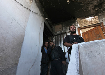 Members of Sheikh Ali Khatib battalion gesture from inside a burnt building, towards a location controlled by forces loyal to Syria's President Bashar al-Assad in Aleppo