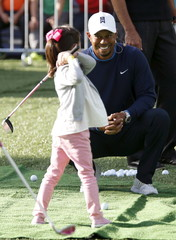 U.S. golfer Woods instructs a girl during a golf clinic in Mexico City
