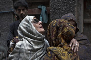 Family members mourn while standing near the body of 62-year-old heart patient Chaudhry Mohammad Gulab outside their residence in Lahore