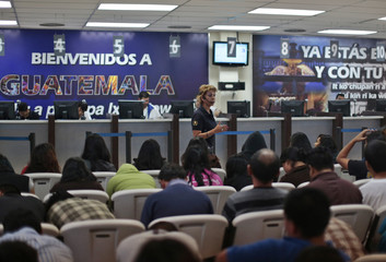 An immigration official explains the re-entry procedures to Guatemalan illegal immigrants deported from the U.S., at La Aurora airport in Guatemala City
