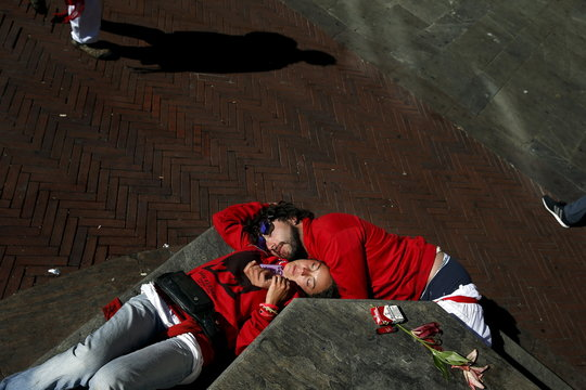 A couple sleeps on the street during the San Fermin festival in Pamplona