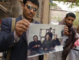 A follower of the Shi'ite Houthi movement holds up a photo outside General Saleh Fadhil's house, which was taken by the group following clashes in the Wadi Dhahr suburb of the Yemeni capital Sanaa