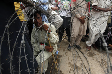 A supporter of Pakistan Tehreek-e-Insaf, a political party led by cricketer-turned-opposition politician Imran Khan, sits with a stick behind the barricade of barbwires upon his arrival with others to participate in the Freedom March in Islamabad