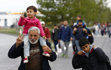 A migrant and his child flash a victory sign as they walk on a highway towards Vienna near Nickelsdorf