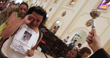 A woman cries holding a picture of her missing dog, as a priest blesses her, at Sao Francisco de Assis Church in Sao Paulo