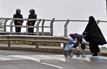 A Muslim woman pushes a baby stroller as Spanish National Police officers stand guard while securing an area during a police operation in Melilla