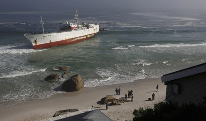 Onlookers walk past a stranded Taiwanese fishing trawler which ran aground in thick fog off Cape Town's popular Clifton beach