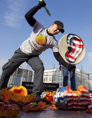 Activists from the Internet Party of Ukraine smash a pumpkin with headphones as they stage a performance in front of the U.S. embassy in Kiev