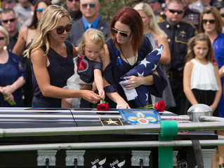 Dawclyn Gerald (C) places a flower on her father's casket, Baton Rouge police officer Matthew Gerald with her mother Dechia at Louisiana National Cemetery, Zachary, Louisiana