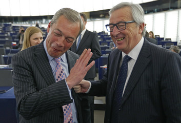Leader of Britain's UKIP and MEP Farage jokes with European Commission President Juncker ahead of a debate on the latest tragedies in the Mediterranean and EU migration and asylum policies in Strasbourg