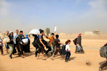 Displaced people flee Samah neighborhood during a fight between Islamic State militants and the Iraqi Counter Terrorism Service in Mosul, Iraq