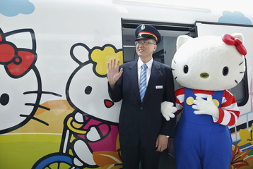 A performer dressed as Hello Kitty, poses with a conductor next to a Hello Kitty-themed Taroko Express train in Taipei, Taiwan