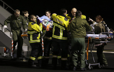 Firefighters and rescue workers carry a wounded Ukrainian protester from a military airplane at Kbely Airport in Prague