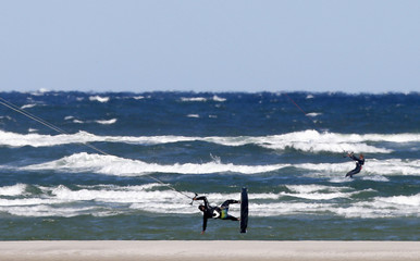 A kite surfer flies off the water off Chapin Beach in Dennis, Massachusetts