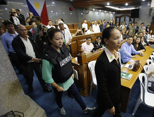 Janet Lim Napoles, wearing a bullet proof vest, is escorted by police agents upon arriving at the Senate in Manila