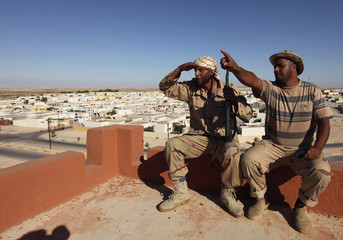 Rebels fighters sit opposite houses in a residential area in Brega