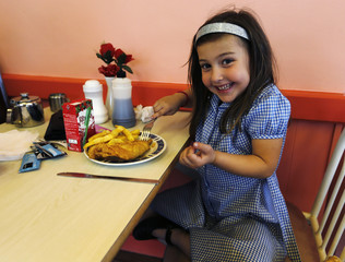 Honey Rose Nettleton-Johnson poses for a picture with her dinner at Jack's Fish & Chips shop in west London