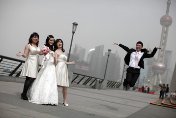 A wedding party pose for pictures with the Oriental Pearl TV Tower in the background on a hazy day in Shanghai